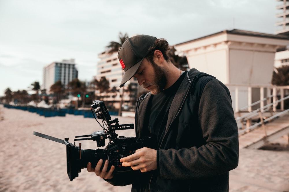 man in black jacket holding black video camera