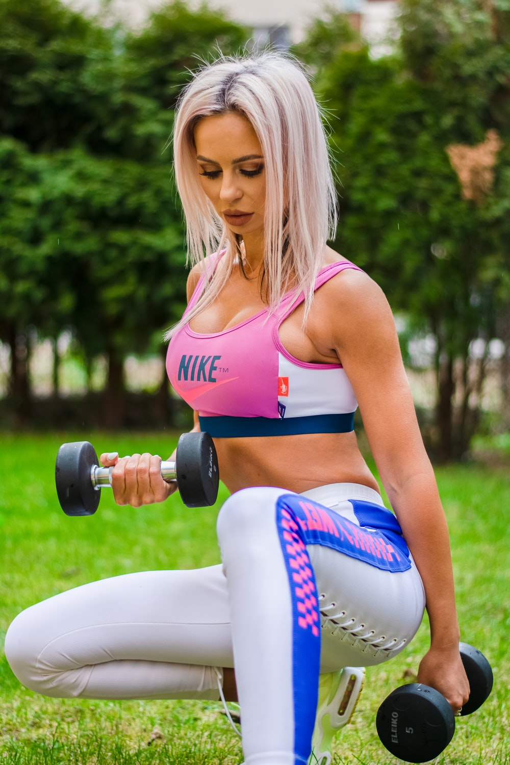 woman in pink sports bra and white leggings sitting on white and black kettle bell