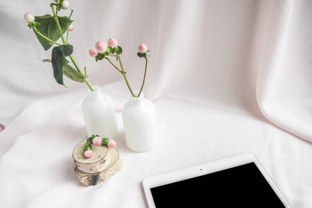 white ceramic vase with red roses