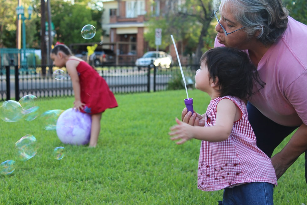 girl in pink and white plaid shirt playing with bubbles during daytime