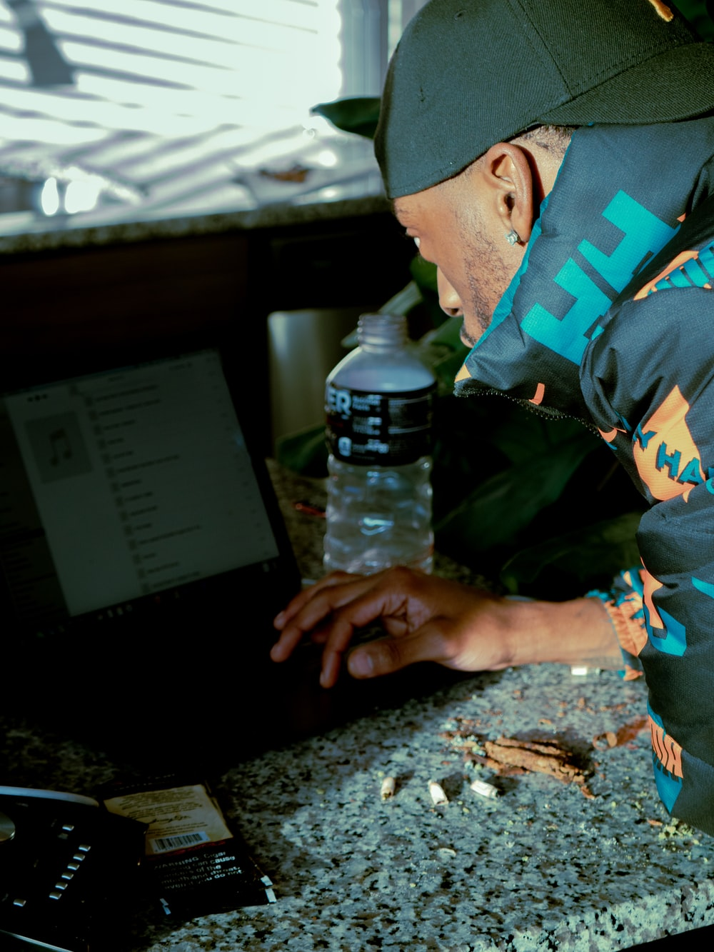 man in green blue and yellow camouflage jacket using black laptop computer