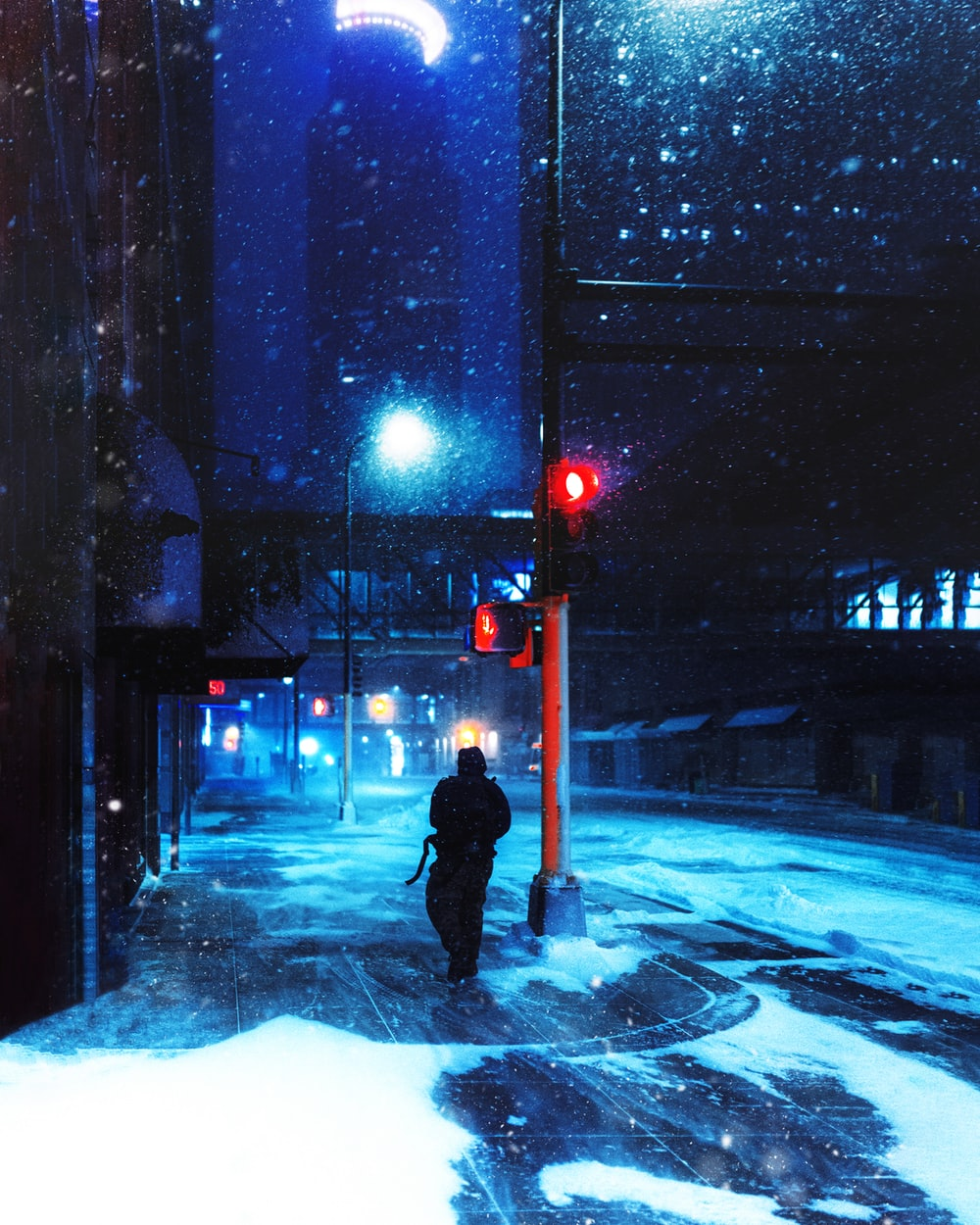 person in black jacket standing on snow covered road during night time