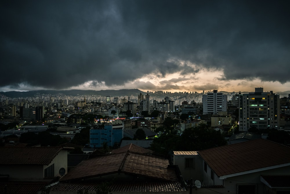 city with high rise buildings under gray clouds during night time
