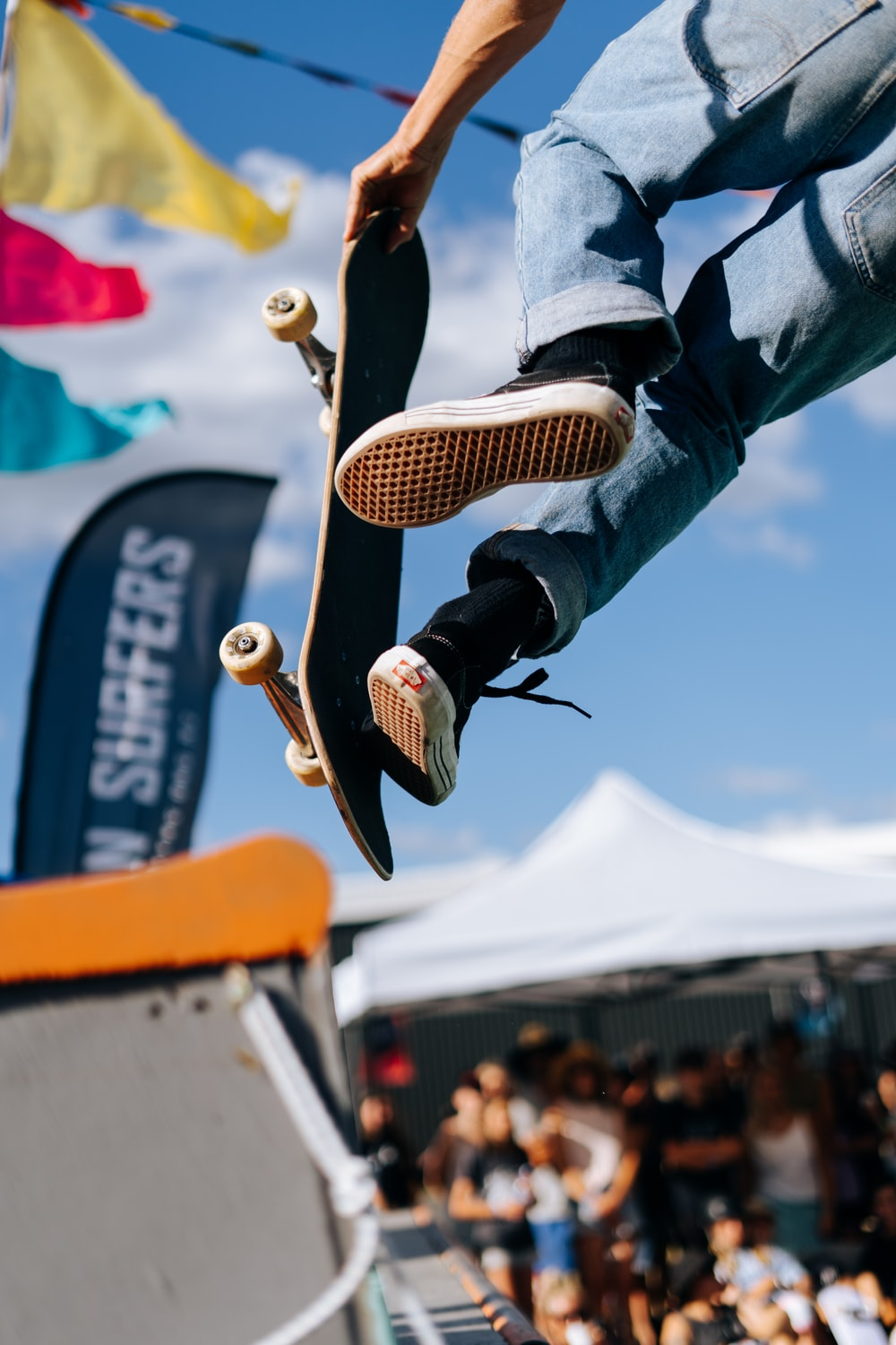 person in blue denim jeans and black and white sneakers jumping on orange and white metal
