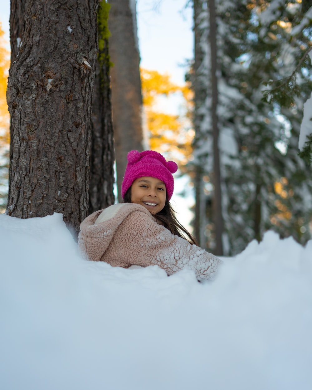 woman in pink knit cap and white knit scarf sitting on snow covered ground near brown