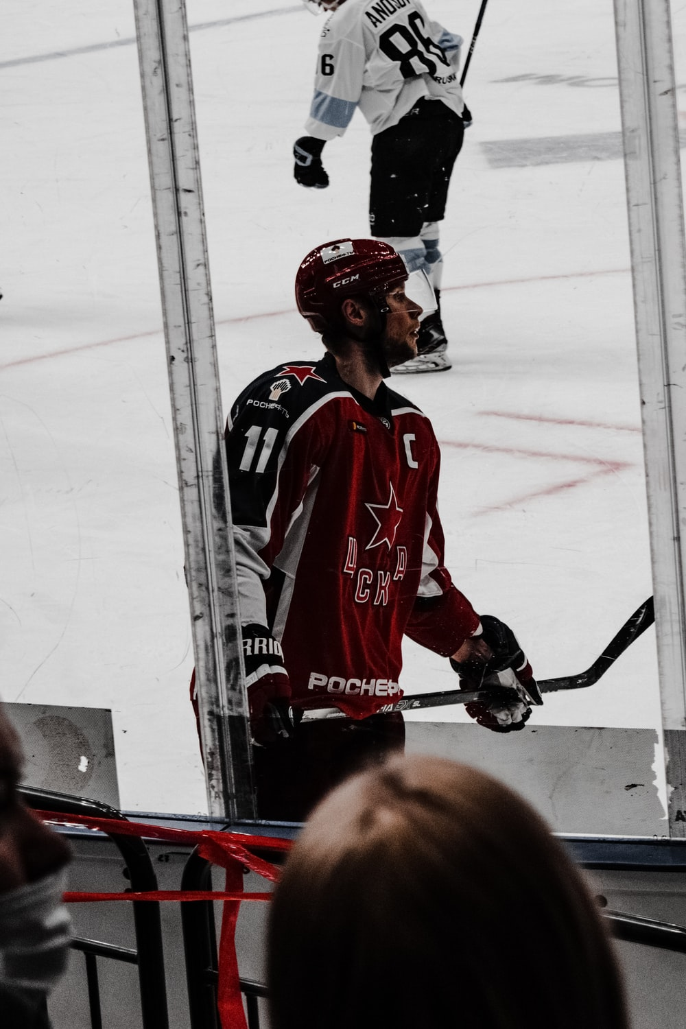 man in red and white jersey shirt playing ice hockey