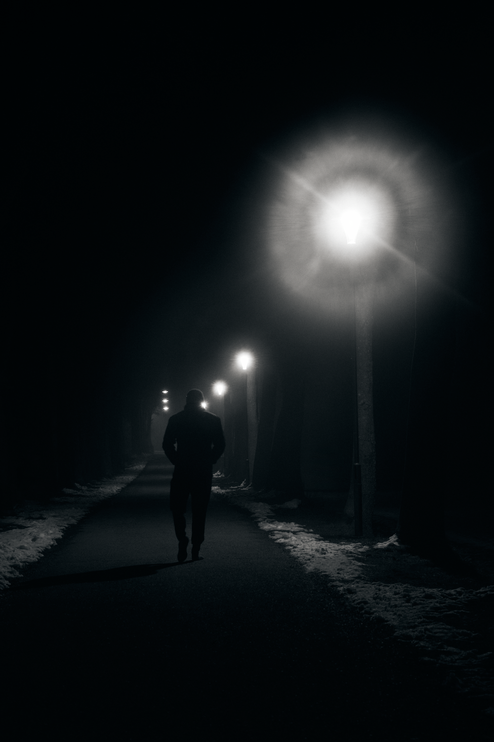 silhouette of man walking on road during night time