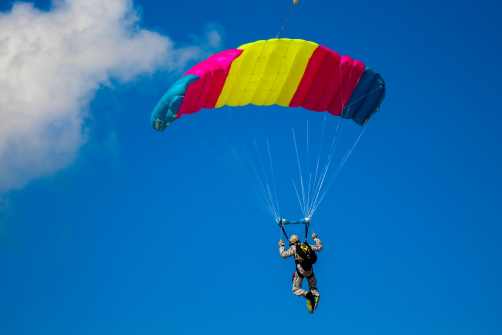 man in black jacket and blue pants riding yellow and red parachute