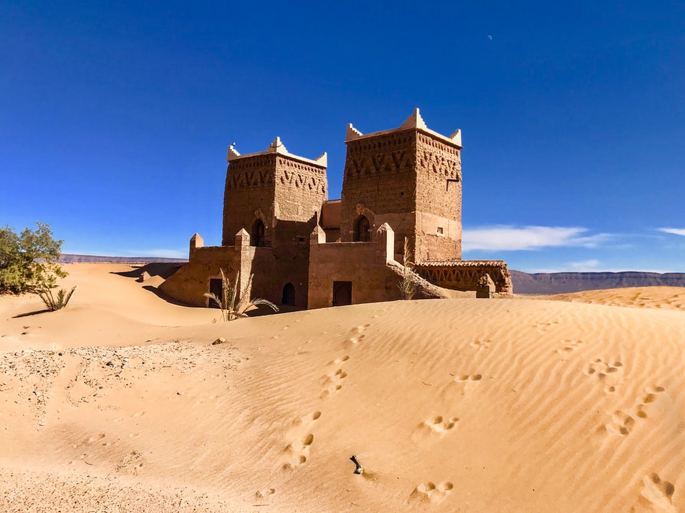 brown concrete building on desert under blue sky during daytime