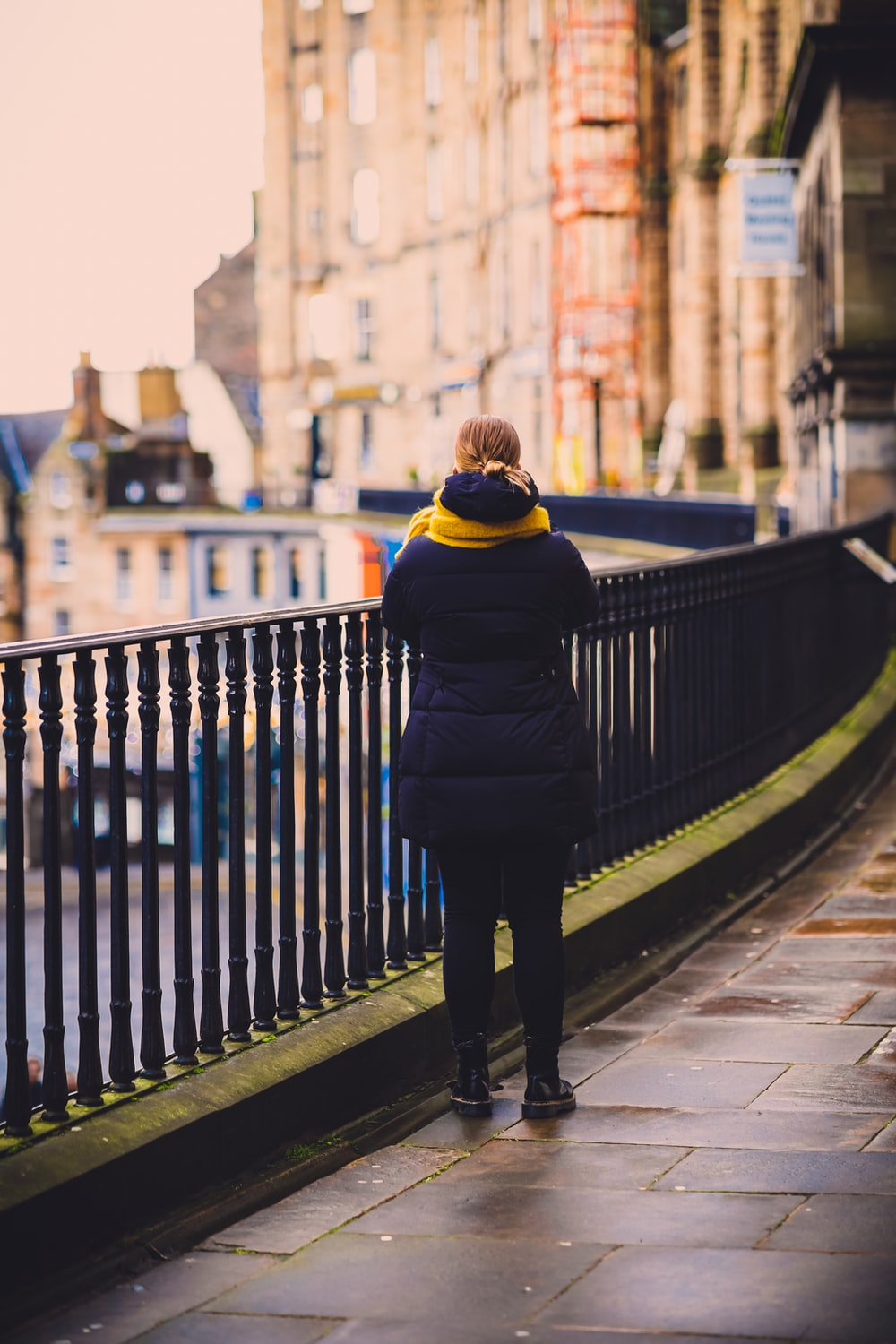 woman in black and yellow jacket standing on sidewalk during daytime