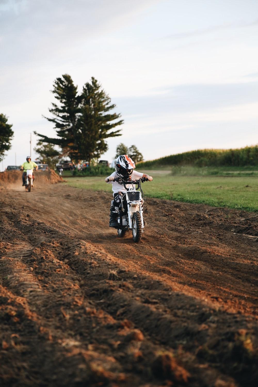 man riding motorcycle on dirt road during daytime