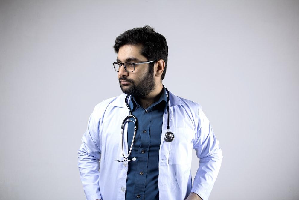 man in white and blue zip up jacket wearing black framed eyeglasses
