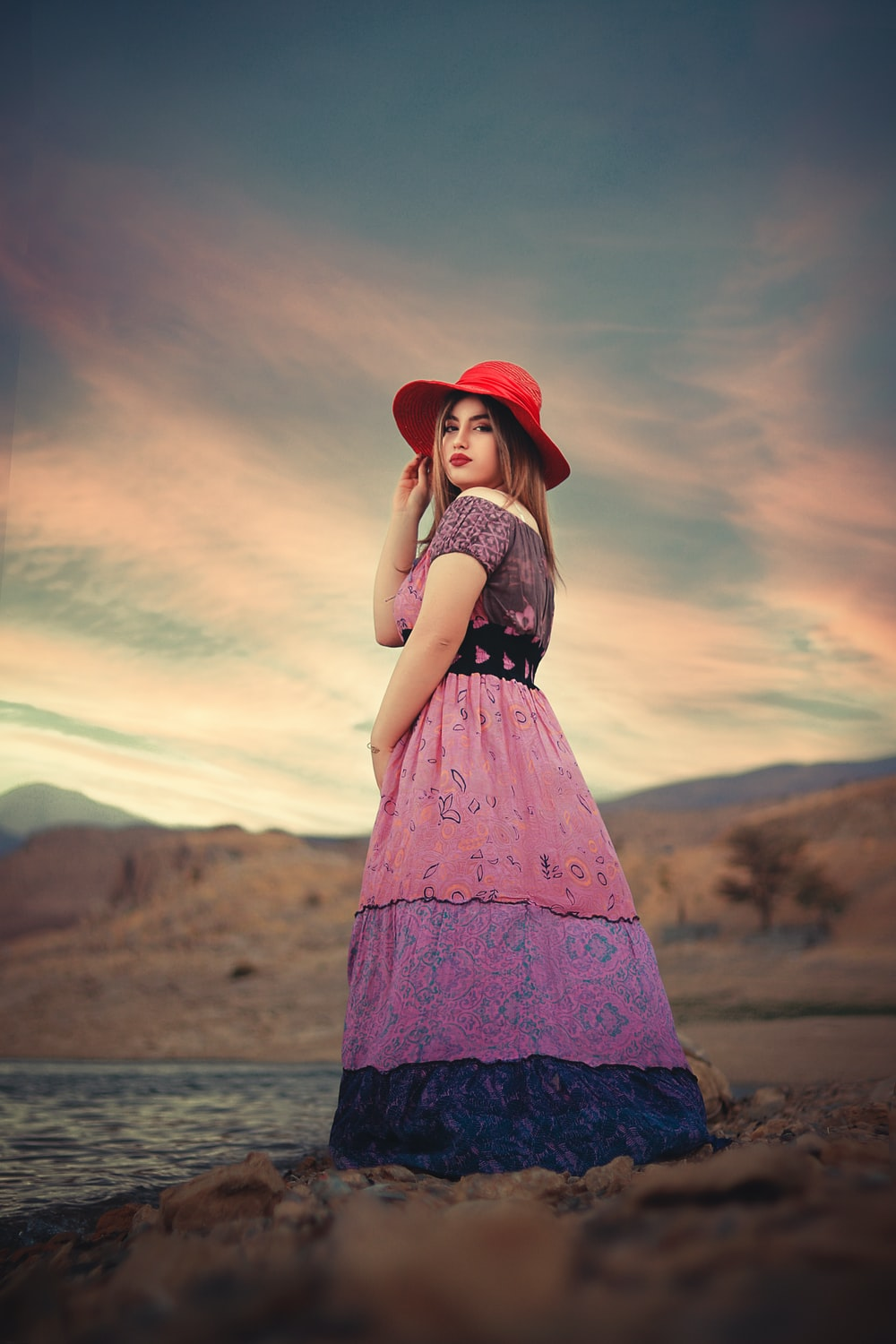 woman in red hat and black and white dress standing on brown field during sunset