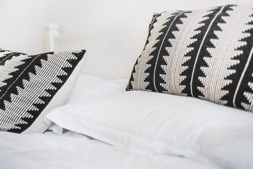 black and white throw pillows on white bed How to Sleep When Pregnant