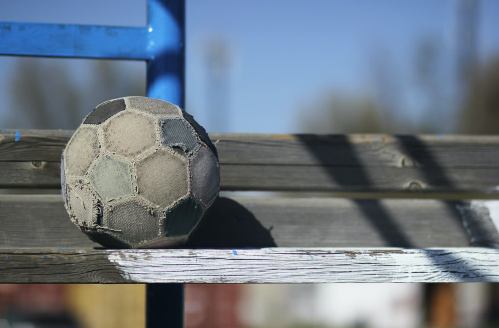 black and white soccer ball on brown wooden plank
