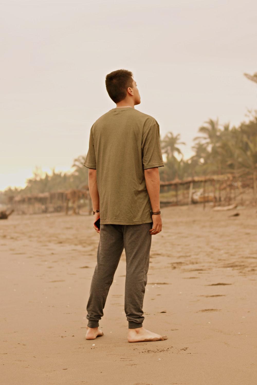 man in brown t-shirt and black pants walking on brown sand during daytime