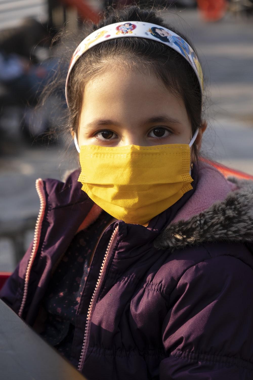 woman in black jacket wearing yellow mask