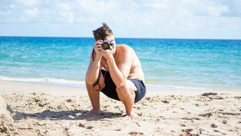 topless man in black shorts sitting on beach shore during daytime