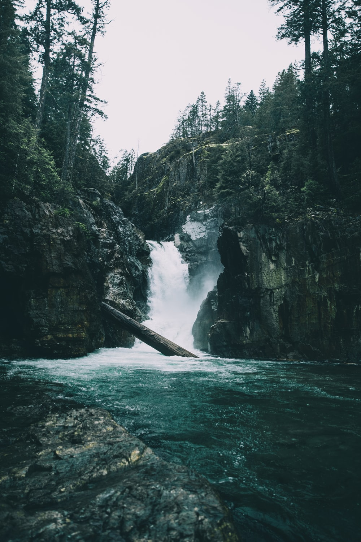 water falls between rocky mountain during daytime