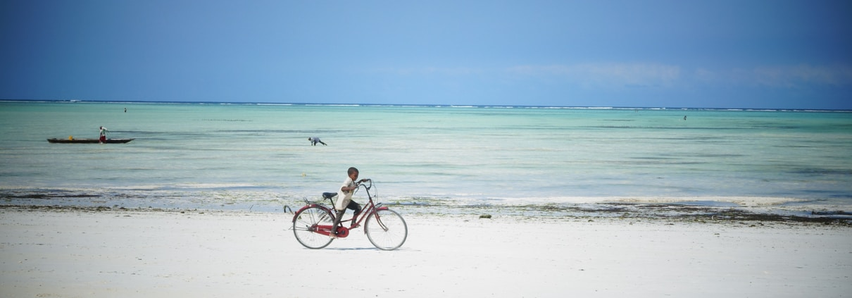 man riding bicycle on beach during daytime