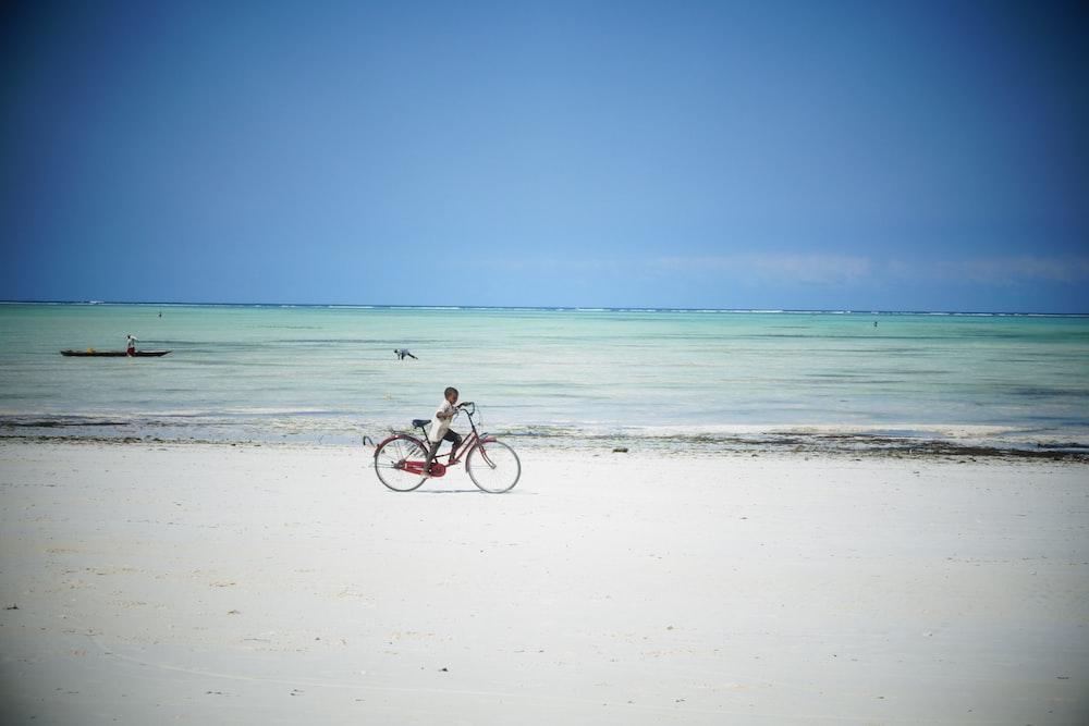 Man Riding Bicycle On Beach During Daytime