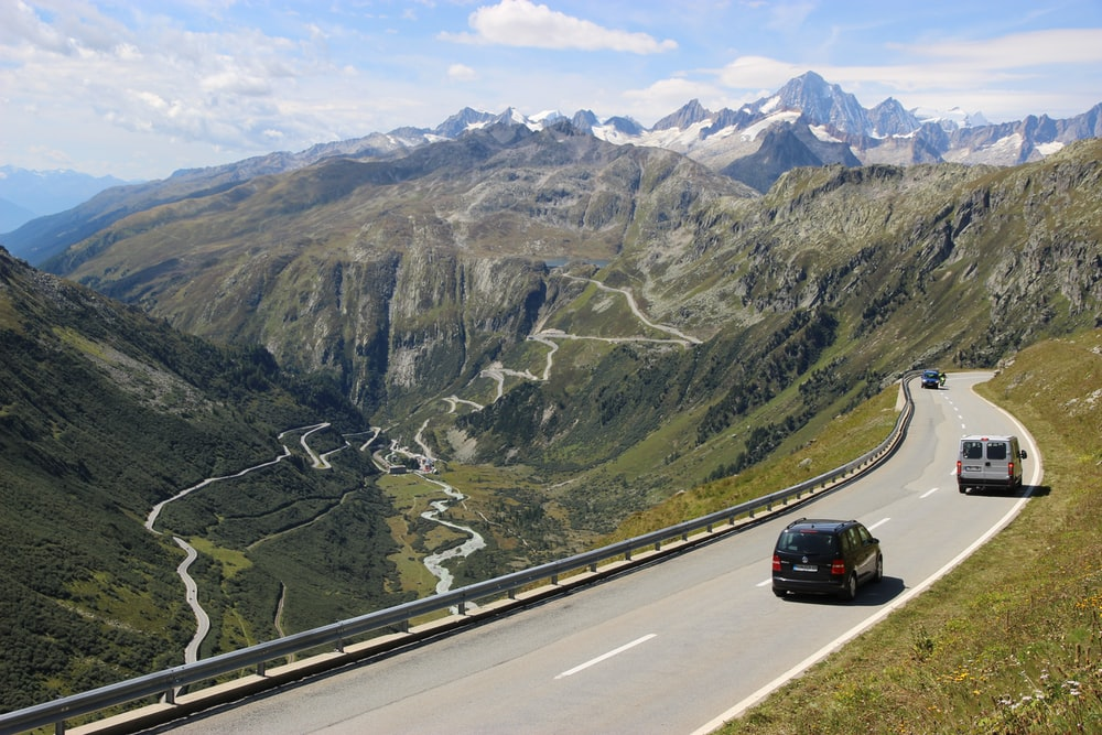 black car on road near mountain during daytime