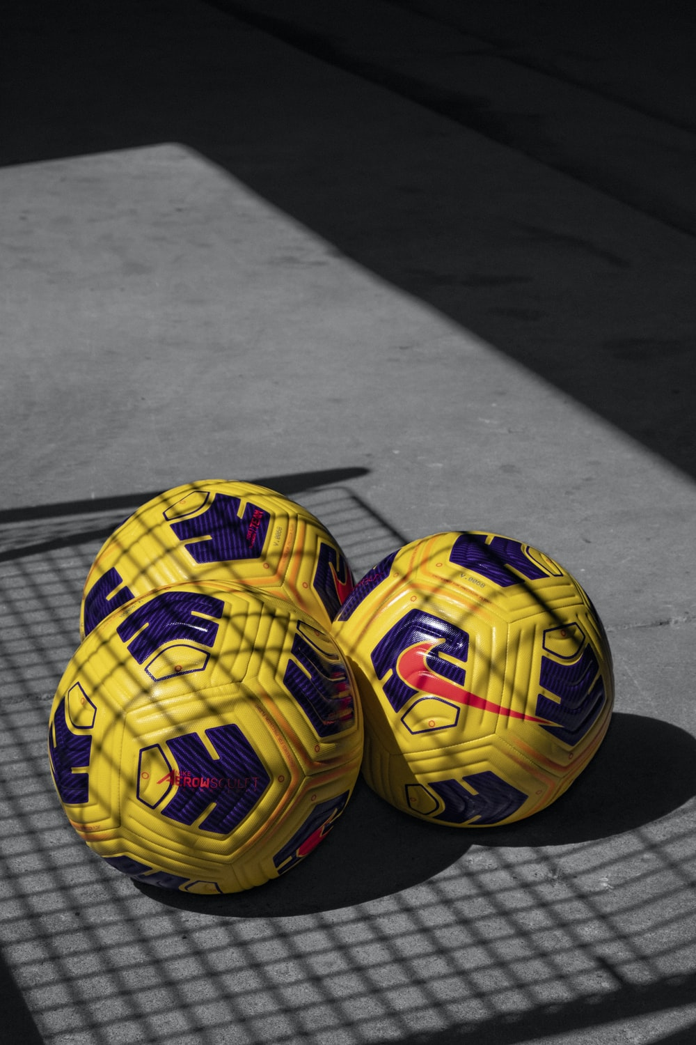 yellow and black soccer ball on gray wooden floor