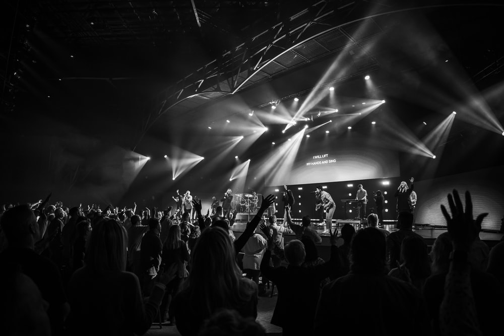 grayscale photo of people standing on stage