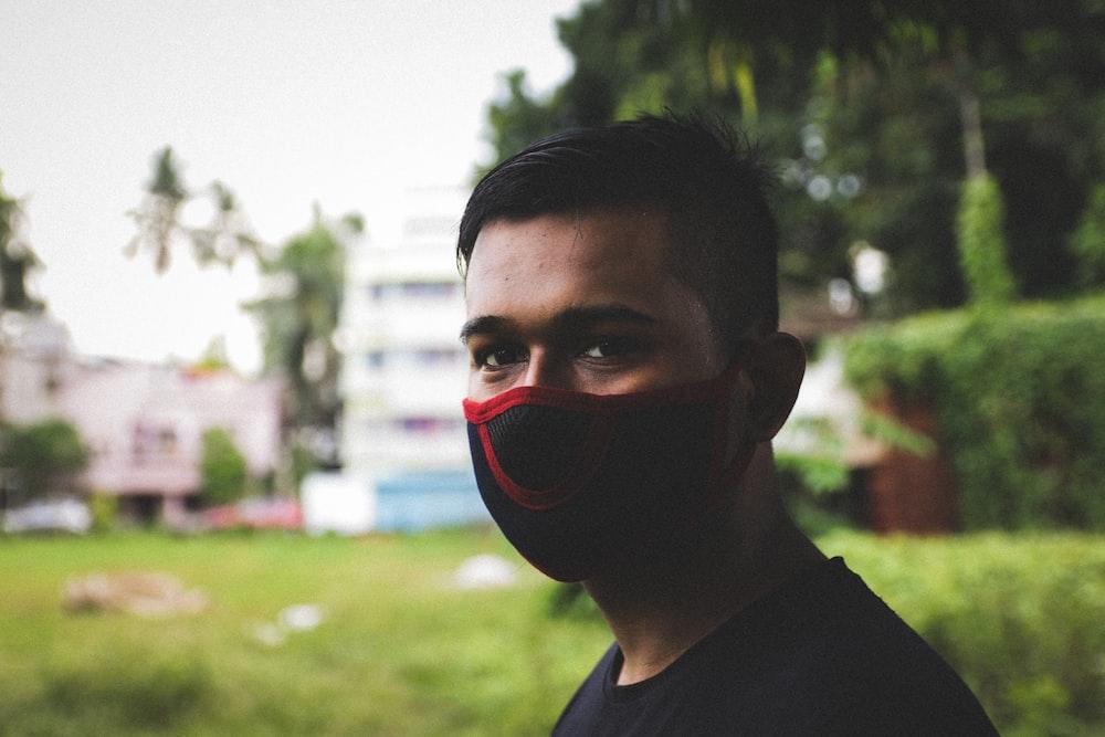 man in black crew neck shirt wearing red mask