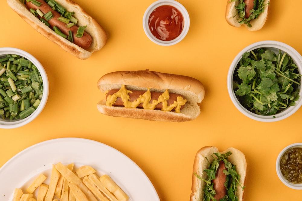 hotdog sandwich with green vegetable on white ceramic plate