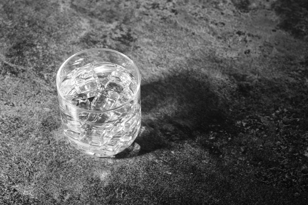 clear drinking glass filled with water and ice cubes