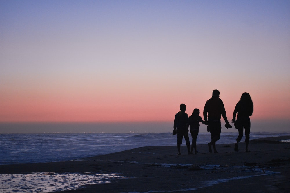 silhouette of 3 men and woman standing on beach during sunset
