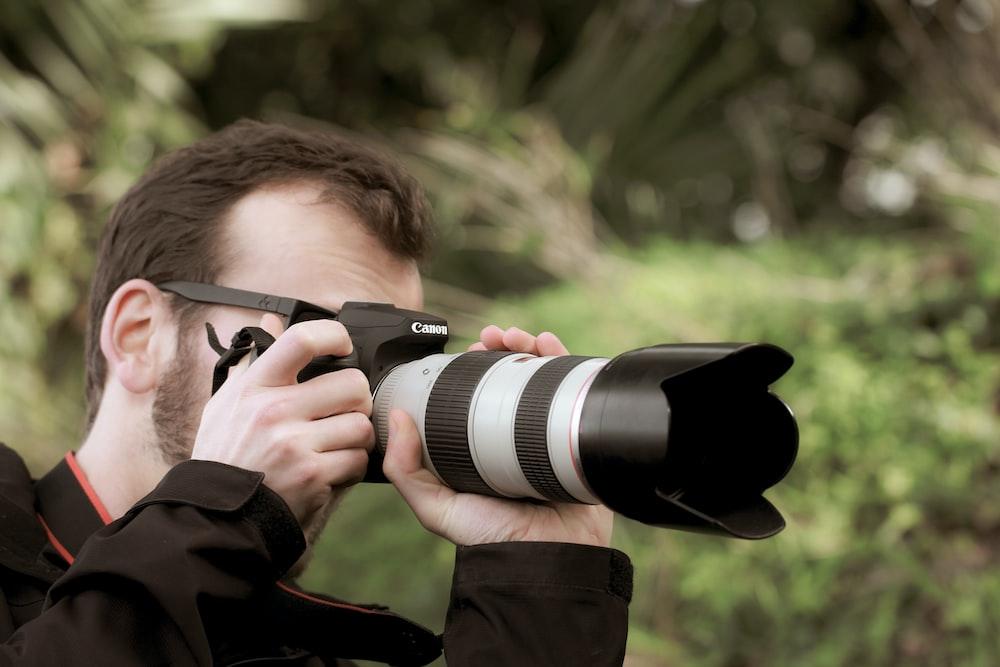 man in brown jacket holding black dslr camera