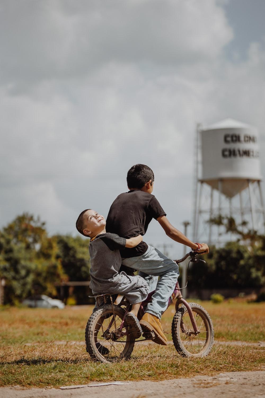 man in black shirt riding on bicycle during daytime