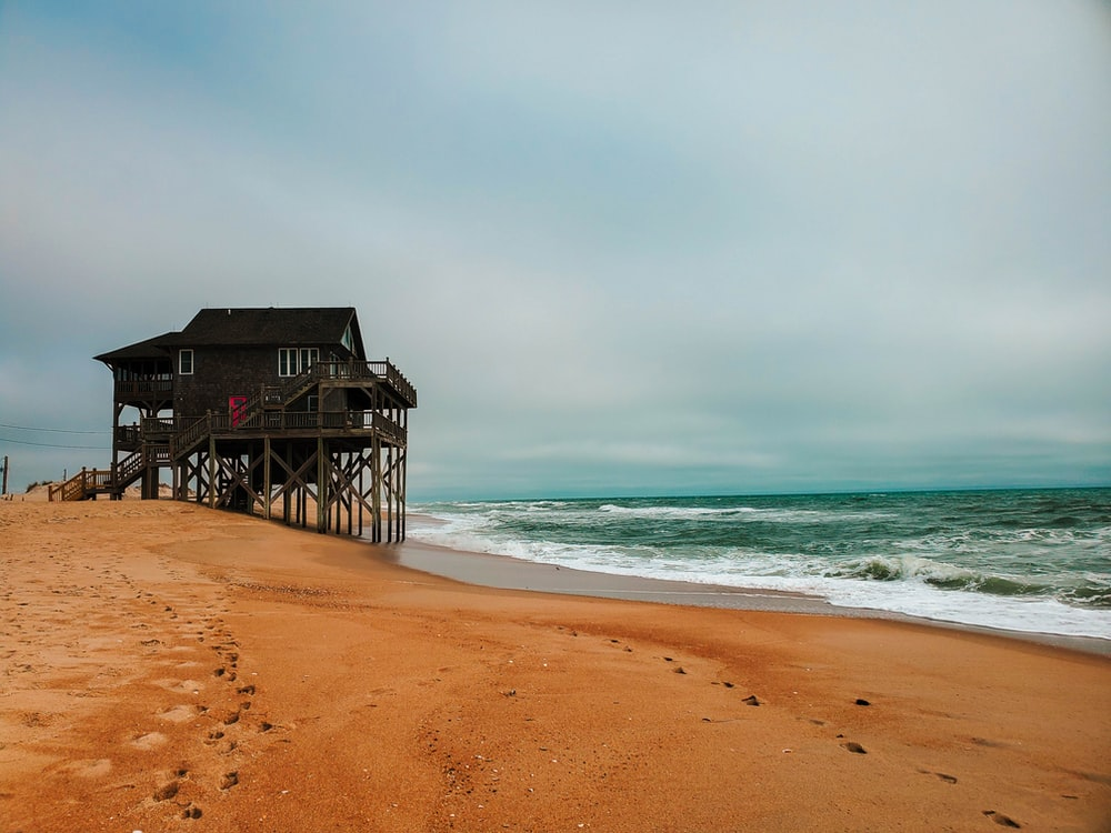 brown wooden house on beach shore during daytime