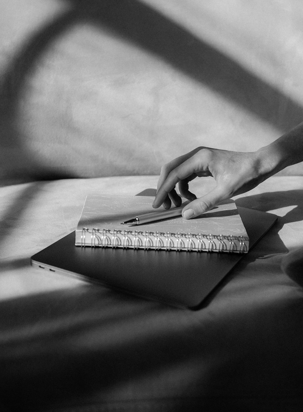 grayscale photo of persons hand on book