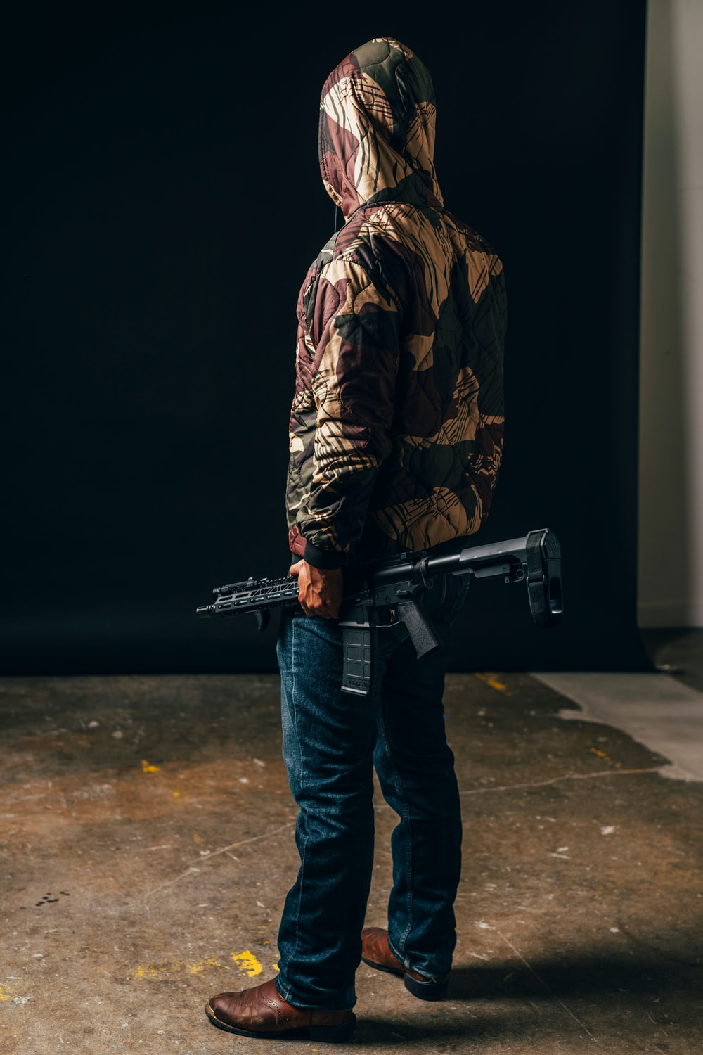 man in brown and black camouflage jacket and blue denim jeans holding black rifle