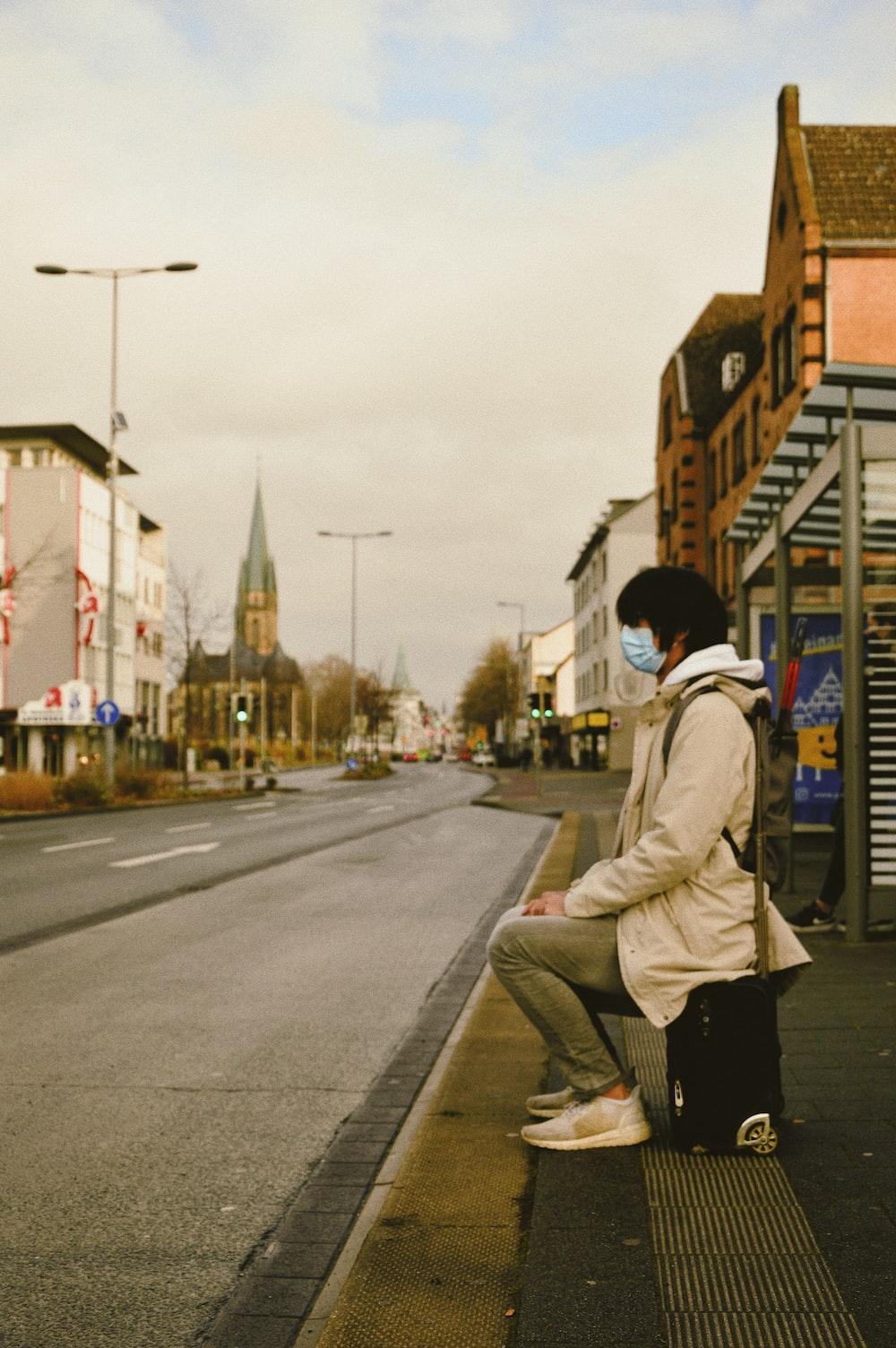 man in white jacket and black pants walking on sidewalk during daytime