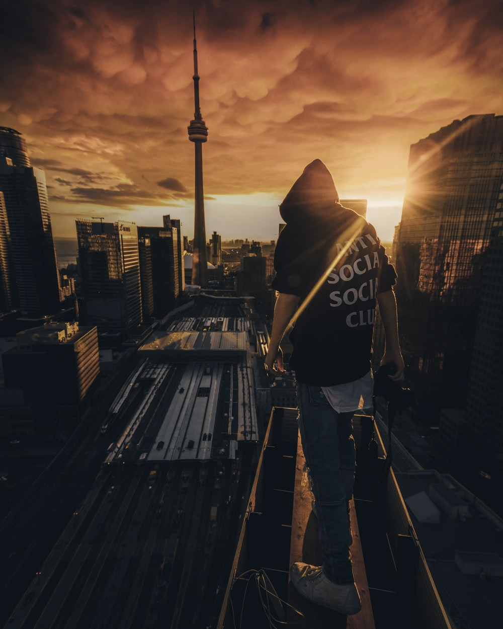 man in black and white hoodie standing on the roof of a building during sunset