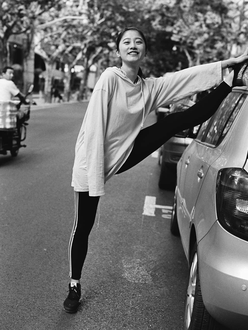 grayscale photo of woman in long sleeve shirt and black pants standing on road