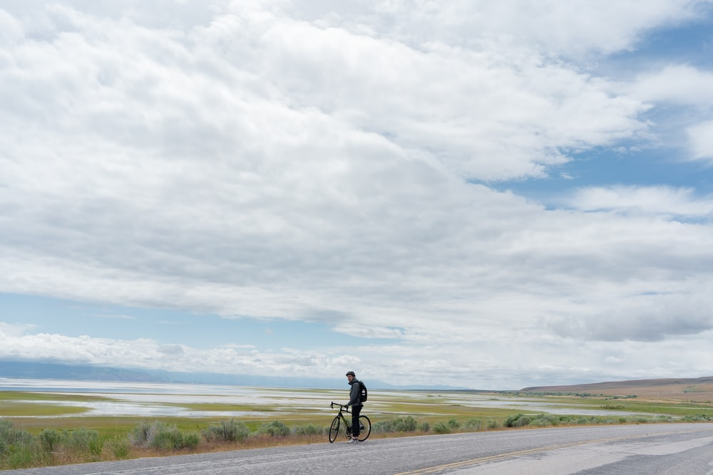man in black shirt and black pants riding bicycle on gray asphalt road under white clouds