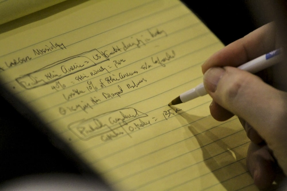 person holding white and black pen writing on yellow paper