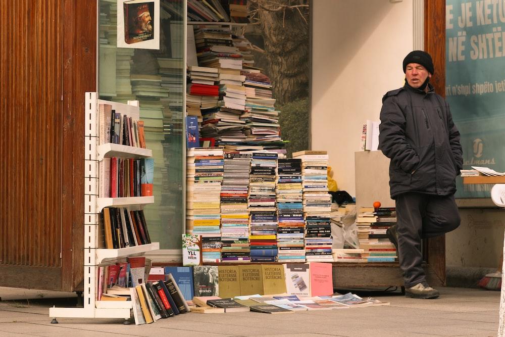 man in black jacket standing near books
