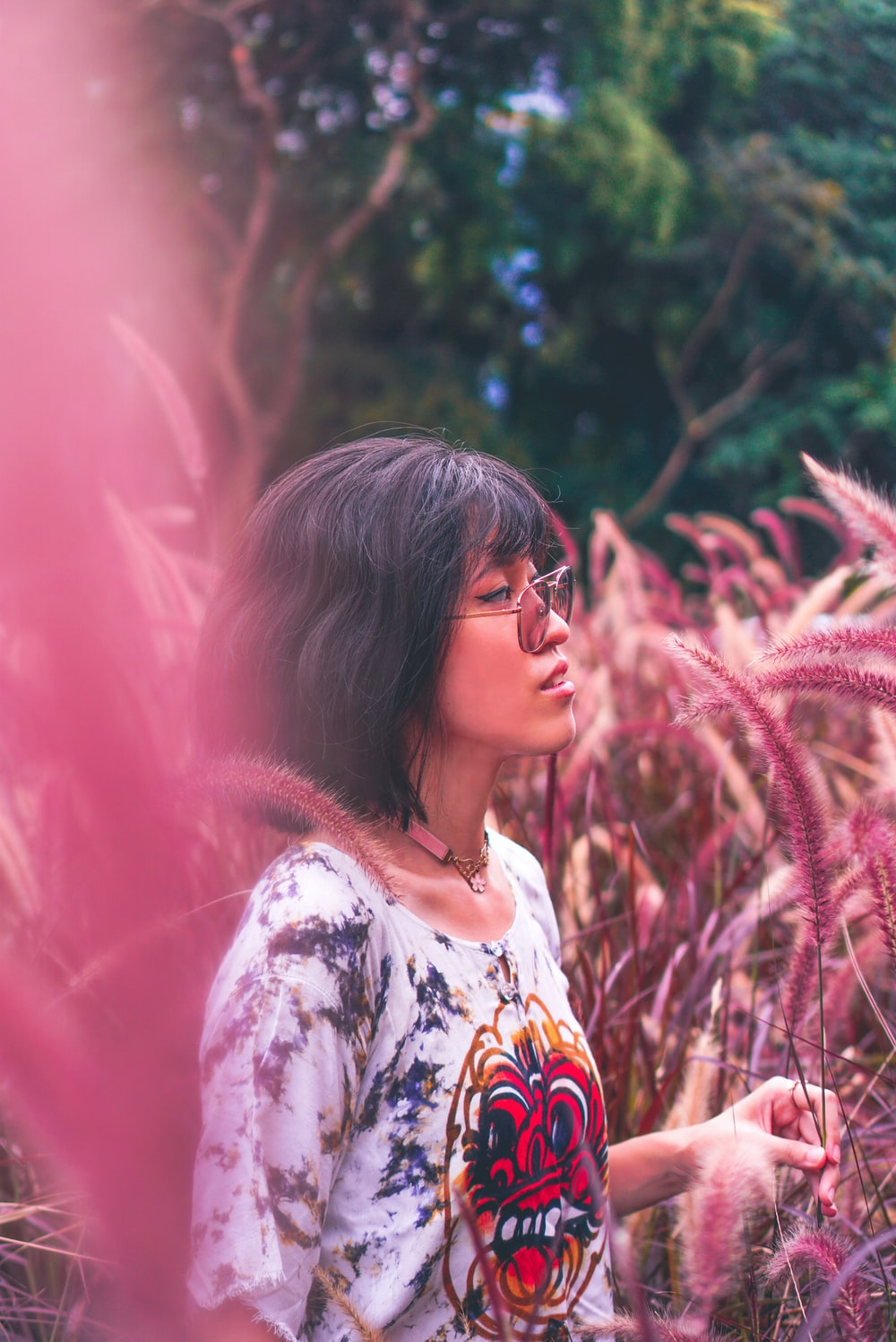 woman in white and yellow floral shirt standing near green plants during daytime