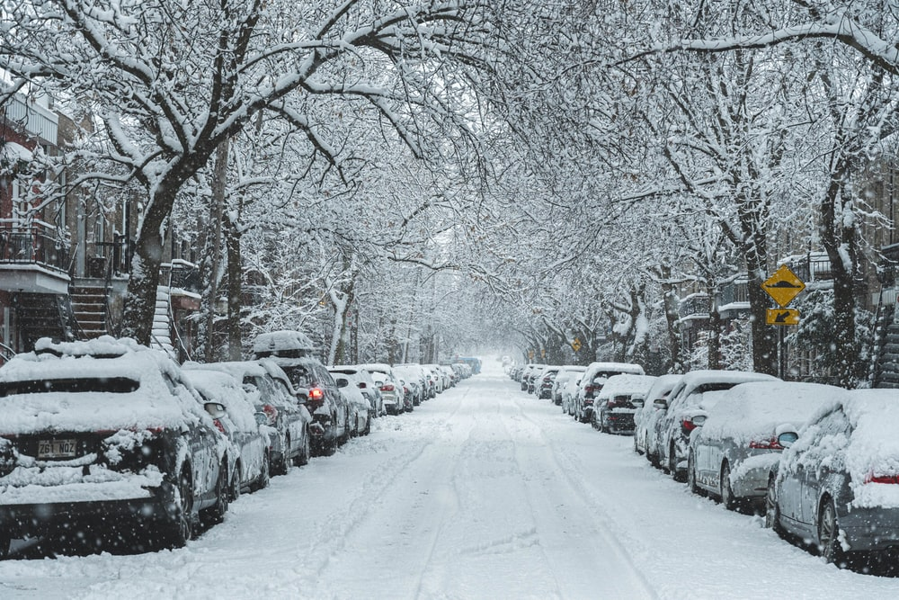 snow covered road with cars parked on side