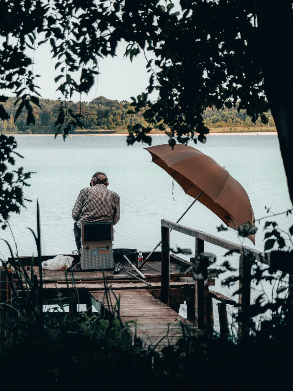 man in gray shirt sitting on brown wooden bench near body of water during daytime