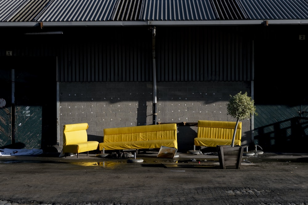yellow and black bench near black wall