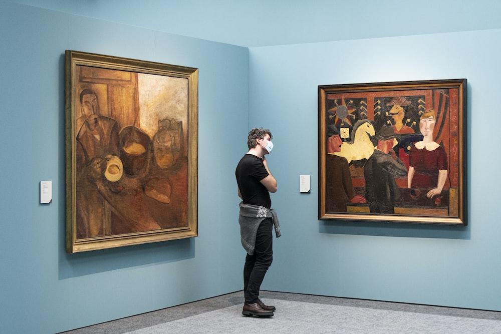 man in black vest standing beside brown wooden framed painting