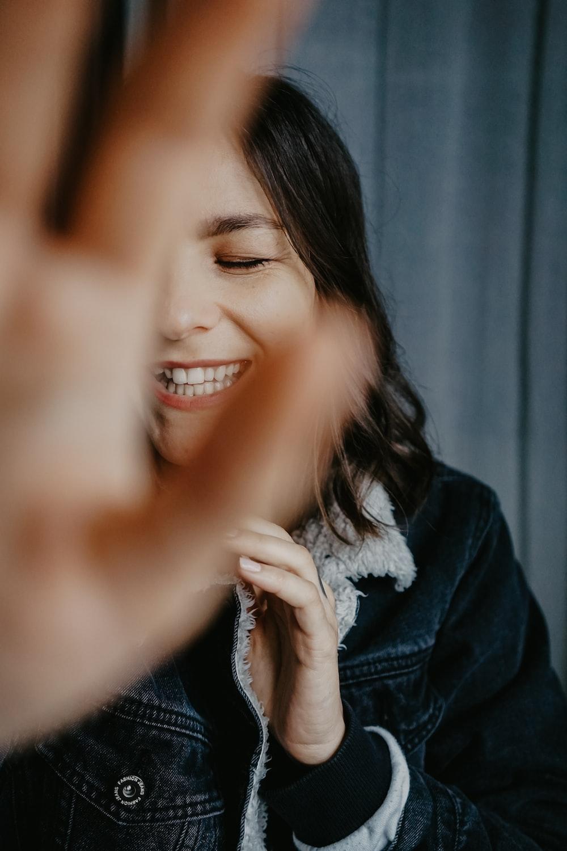smiling woman in blue denim jacket