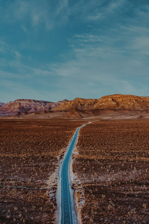 gray asphalt road between brown mountains under blue sky during daytime